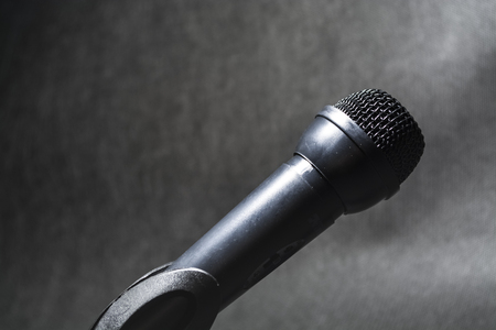 The electric microphone on a monophonic black background. Equipment for the singer or blogger. Music. Archivio Fotografico