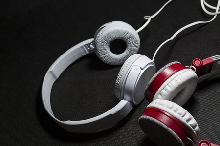 White big earphones for listening of music. For phone. Skin. Black background. Portable. Beautiful and fashionable.