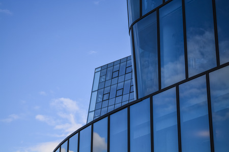 Modern architecture of office buildings. A skyscraper from glass and metal in the form of a curved wave. Reflections in windows of the blue sky and houses.