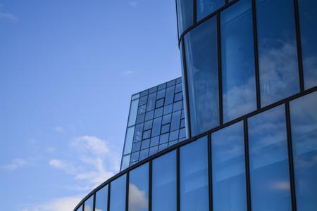 Moderne architectuur van kantoorgebouwen. Een wolkenkrabber van glas en metaal in de vorm van een gebogen golf. Reflecties in ramen van de blauwe lucht en huizen.