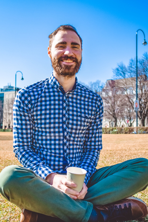 The young guy with beard and in shirt sits on grass having crossed legs in the spring park and has coffee from paper glass. Cheerful mood. Blue sky.