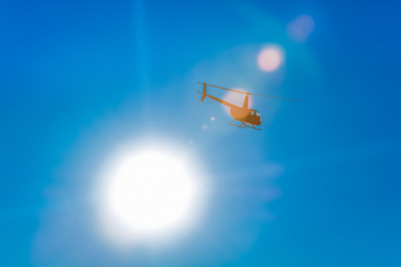 Silhouette of helicopter in blue clear sky with solar patches of light. Warm spring day. Transport.