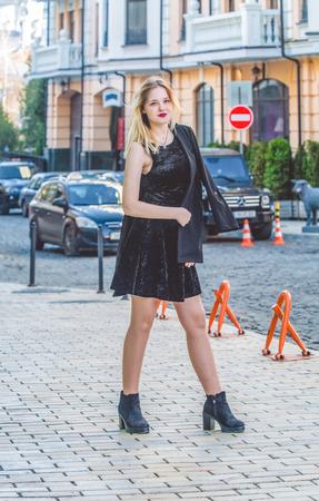 Das junge Mädchen in schwarzer Kleidung im sonnigen Frühlingstag spaziert auf den Straßen der Altstadt. Kleid, Jacke und Mantel. Mode. Standard-Bild
