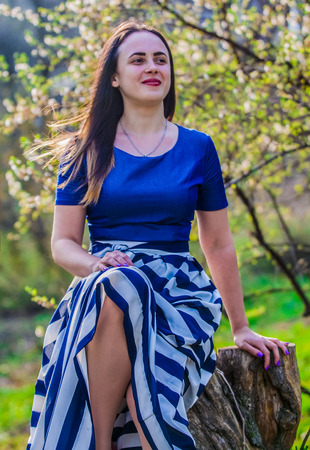 The young girl in dress with long skirt walks in the spring park. The beautiful nature in April. Sunny weather. Фото со стока
