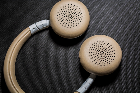 On black monophonic background lie big earphones for listening of music. Modern technologies and gadgets 스톡 콘텐츠