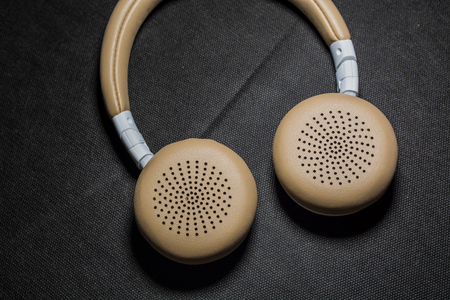 On black monophonic background lie big earphones for listening of music. Modern technologies and gadgets 写真素材