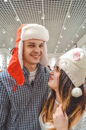 The loving young couple plays the fool with different objects in shop. Positive emotions and fun. Shopping Imagens