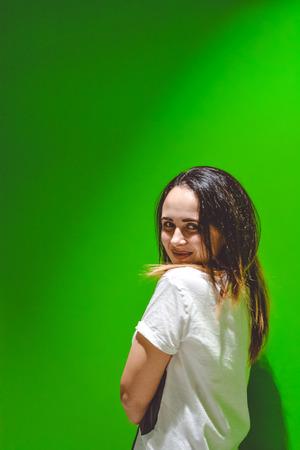 The young girl costs one on a monophonic green background and smiles Stock Photo
