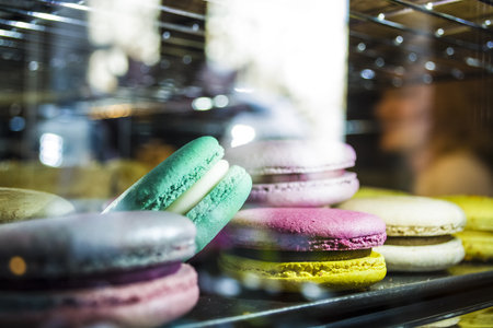 Glass show-window with illumination in coffee shop with multi-colored French macarons. Tasty sweets. 写真素材