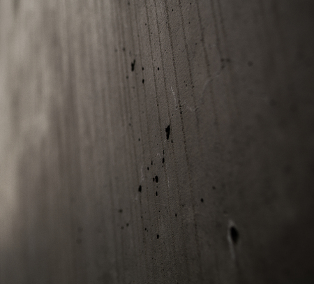 Gray monophonic background with textural holes in a concrete wall with cracks and drips