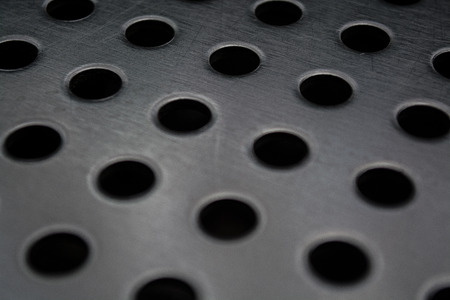 Gray monophonic background with big quantity of holes in a metal plate. Surface. Texture