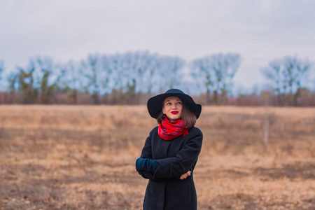 The girl in a black coat, a shovel hat and with red lipstick on lips, walks in the park. Style and modern fashion Reklamní fotografie
