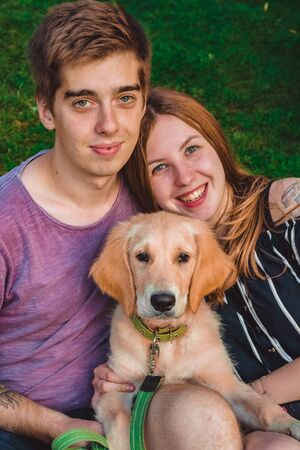 The young married loving couple walks with the little dog in the park. Golden retriever