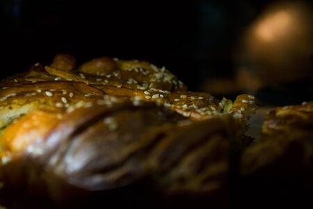 Tasty home-made pastries. Salty sesame pie. Black background