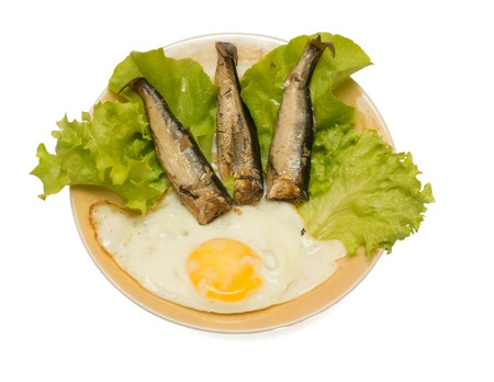Smoked herring with fried egg and salad isolated on white background