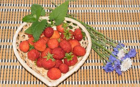 lemon balm: fresh strawberries in a basket heart shape on a wooden table