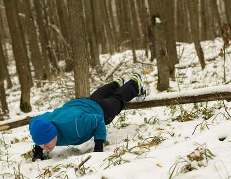 man performs exercise in the winter woods. Healthy lifestyle concept.