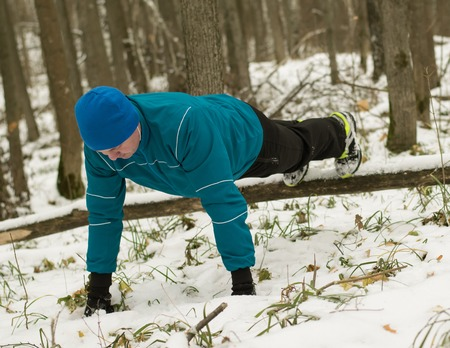 cross legs: man performs exercise in the winter woods. Healthy lifestyle concept.