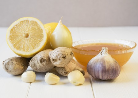 The root of ginger and honey on white wooden table. The concept of treatment with natural products. Stock Photo