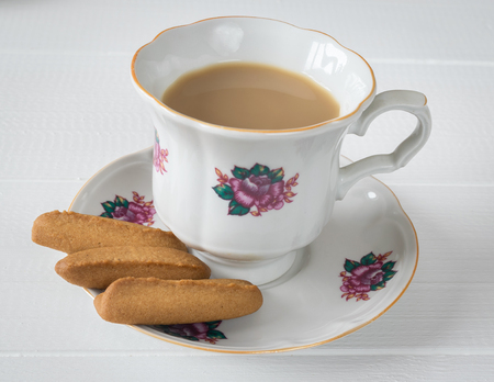 nudelholz: Gingerbread cookies with a cup of coffee on a white wooden table. Homemade baking.