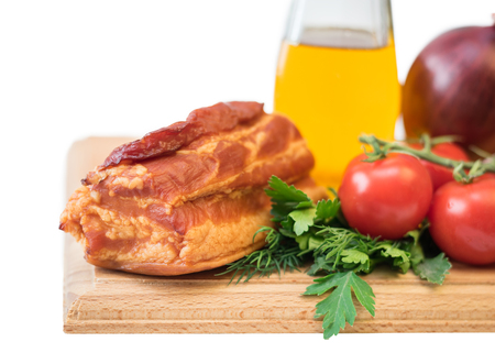 Smoked pork with spices on a wooden board isolated on white background. Still life of meat dishes.