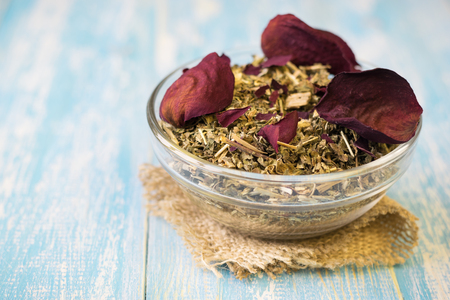 potpourri: Herbal tea with rose petals on a rustic table. Stock Photo