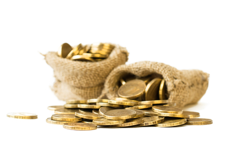 Metal coins poured from a bag on a white background. The concept of storage of money. Stock Photo