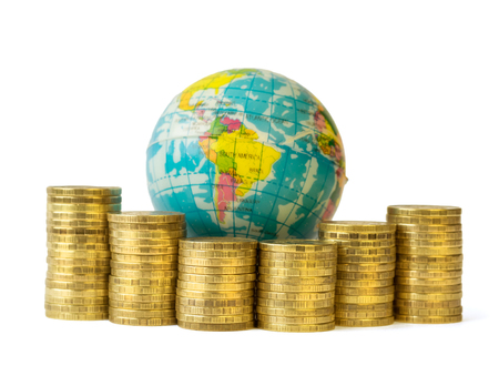 developed: Metal coins and globe isolated on white background. The concept of budget travel. Money rules the world.
