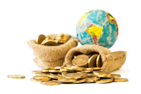 banco mundial: Monedas de metal y globo aislado sobre fondo blanco. El concepto de viaje presupuestario. El dinero gobierna el mundo. Foto de archivo
