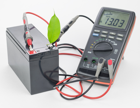 Rechargeable battery with connected measuring instrument and green leaf. The concept of clean energy. Stock Photo