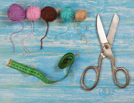 kit de costura: Vintage scissors, balls of wool and tape measure on a blue wooden table. The concept of home handicraft. Foto de archivo