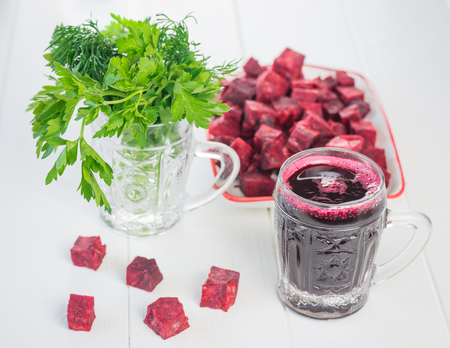 Beet juice with green onions and parsley on a white wooden table. The concept of a healthy vegetarian diet. Stock Photo