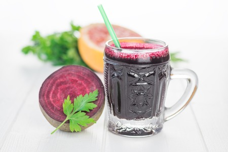 Beet smoothie with grapefruit and parsley on a wooden table. The concept diet food for weight loss.