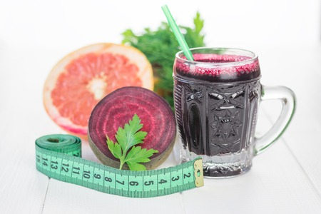 rid: Measuring tape with beet juice and grapefruit on a white wooden table. The concept of diet for getting rid of excess weight. Stock Photo
