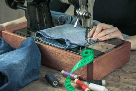 black appliances: Sewing machine of the past with thread and scissors. The concept of home production and repair of clothing.