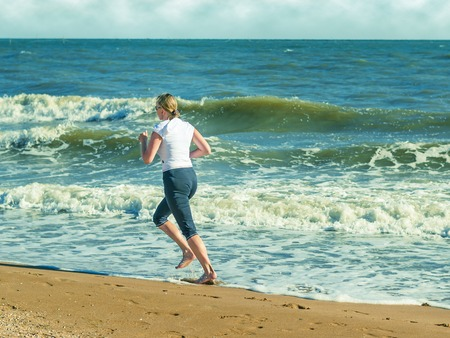 A woman performs morning run on the beach. Sports the ocean.