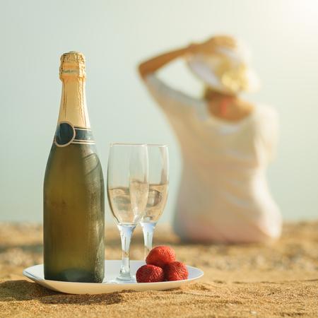 Eine Flasche Sekt mit Brille auf einem weißen Teller. Sandy Sommer Strand in der Sonne. Standard-Bild - 82677598