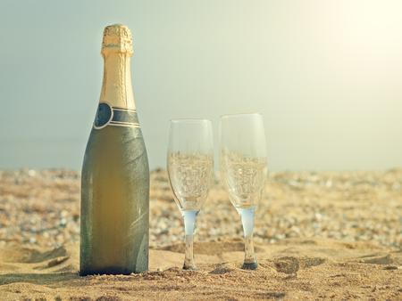 Eine Flasche Sekt mit Brille auf einem weißen Teller. Sandy Sommer Strand in der Sonne. Standard-Bild - 82937964