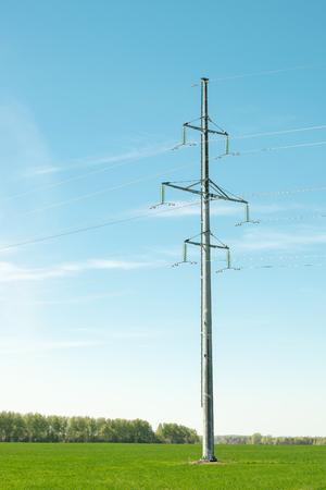 Ondersteuning hoogspanningslijn op blauwe hemelachtergrond. Apparatuur voor het overbrengen van elektrische stroom van hoogspanning.