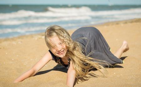 Het meisje in de grijze jurk op het zand bij de oceaan. Portret van vrolijke meisjes spelen met zand en wind uit de zee.