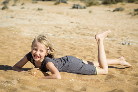 Little girl in gray dress is resting on the hot sand. The concept of fun in itema the summer holidays. Stock Photo
