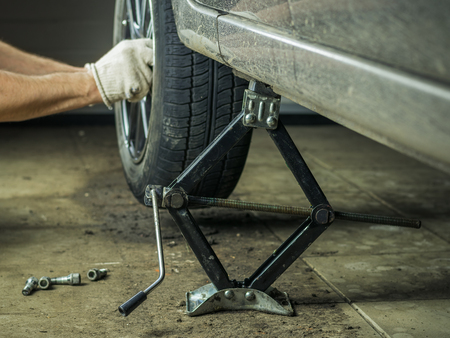 garage: A man with gloves on repairing the rear wheel of the car. Stock Photo