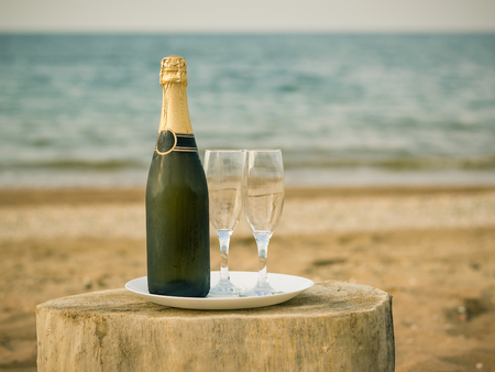 A bottle of cold champagne glasses and strawberries on a sandy beach. The concept of summer a romantic dinner. Stock Photo
