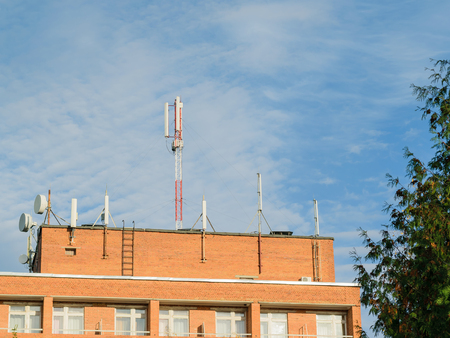 Antennas mounted on the roof of a residential brick house. Providing the residents of the house mobile phones and the Internet.