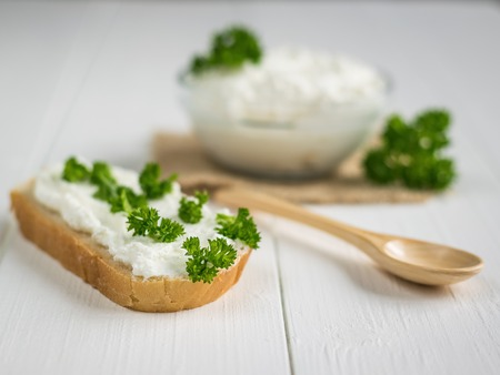 A fresh slice of bread smeared with cottage cheese cream with parsley on the table. The concept of a healthy diet. Stock Photo
