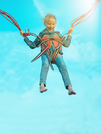 Happy girl tied with belts swinging the attraction closed from fear through the eyes. The child in the amusement Park. Stock Photo