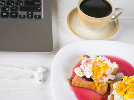 Beige coffee Cup and toasted French bread with curd cream, plum jam and orange zest.
