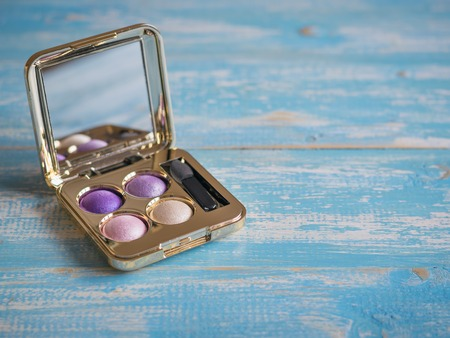 Eyeshadow, brush, lipstick on a vintage wooden table. Set of beautiful womens cosmetics on the table.