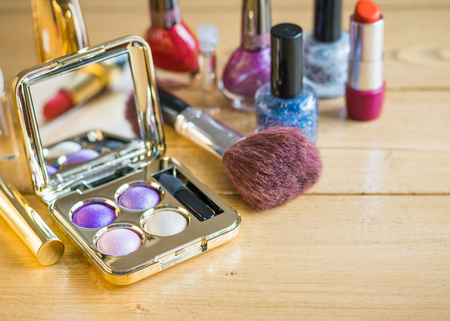Eyeshadow, brush, lipstick on a vintage wooden table. Set of beautiful women's cosmetics on the table.
