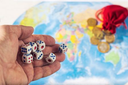 Male hand throwing dice on the table with a world map and money. The concept of ownership of the world. World order. The control population.